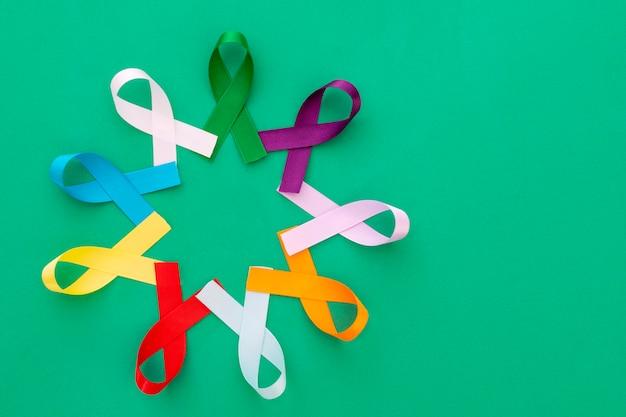 Círculo com fitas coloridas de campanhas de prevenção de doenças e câncer com fundo verde e espaço para texto
