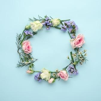 Círculo de arranjo de flores de rosas, eustoma e capim-limão no azul
