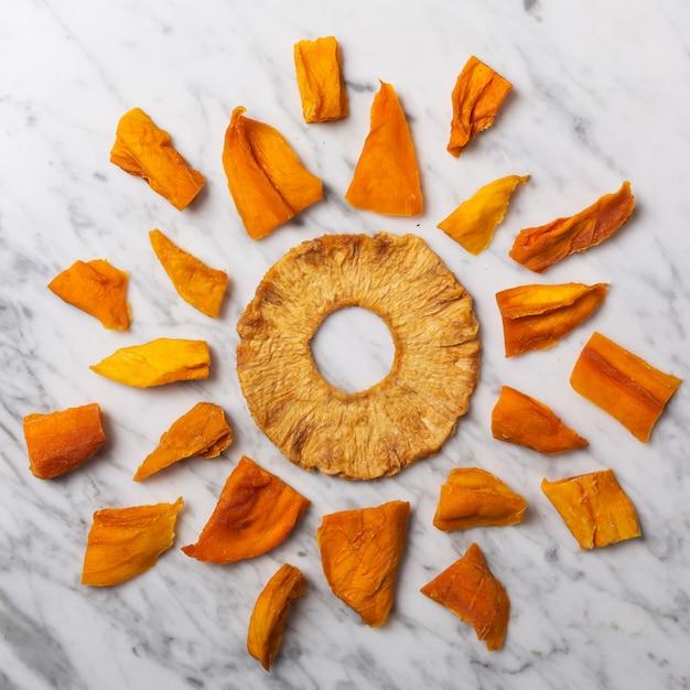 Círculo de comida feita com chips de manga e abacaxi em uma mesa de mármore