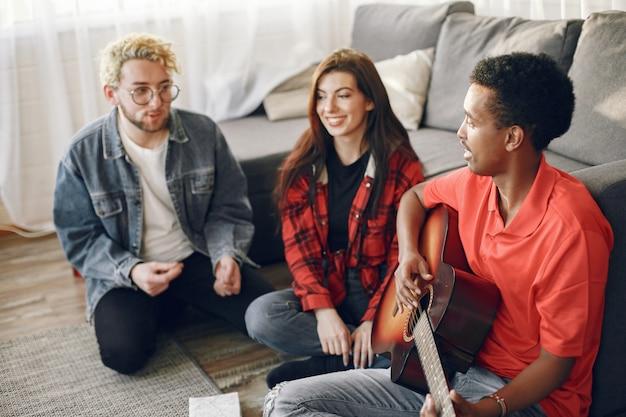 Círculo de diversos frineds reunidos em casa. um cara cantando enquanto tocava violão.