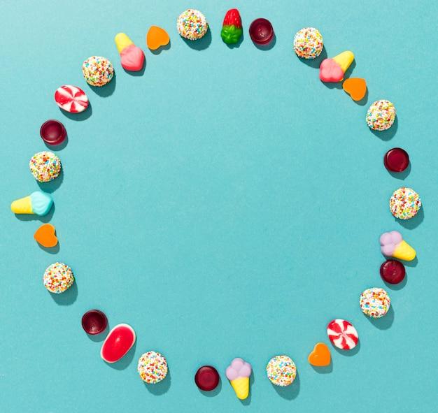 Círculo de doces coloridos sobre fundo azul