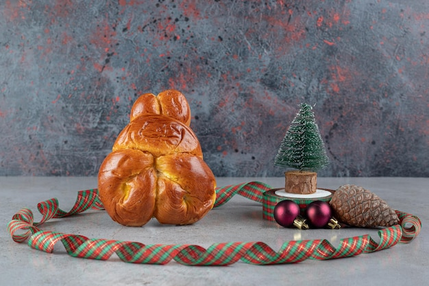 Círculo de fita colorida em torno de um pão doce e decorações de natal na mesa de mármore.