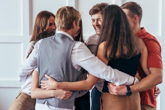 Círculo de jovens se abraçando.