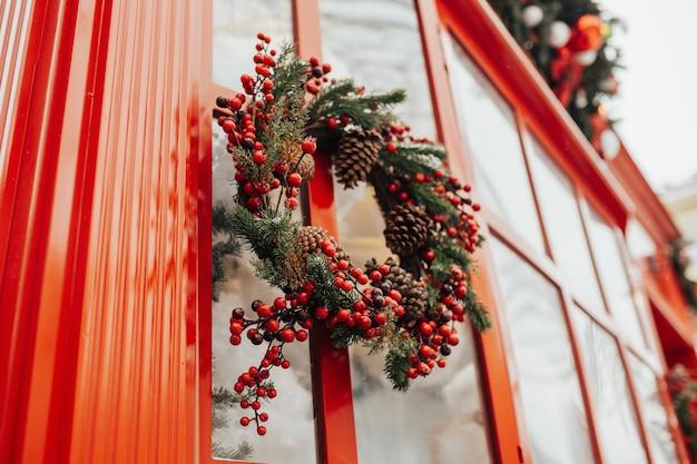 Círculo de ramos de abeto na janela com tema de natal ao ar livre