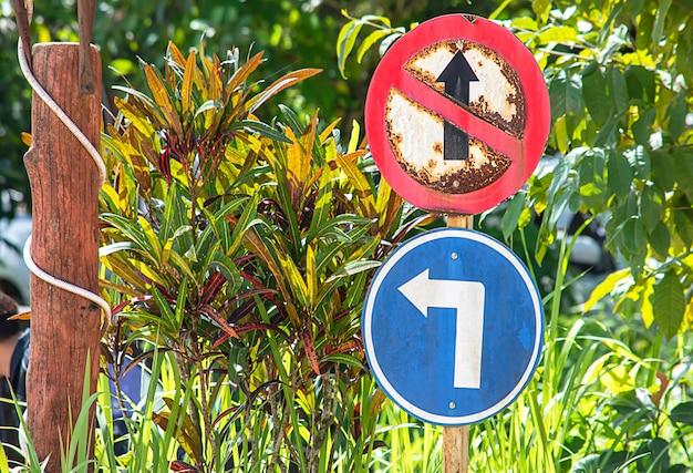 Círculo de sinal de trânsito que é proibido seguir em frente e virar à esquerda árvore embaçada de fundo.