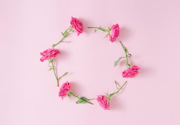 Círculo floral em fundo rosa. quadro redondo de rosas cor de rosa. composição de arte floral minimalista. copie o espaço.