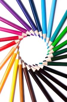 Círculo ou redemoinho de arco-íris de lápis de cor em uma superfície branca no centro, espaço de cópia, simulação, símbolo lgbt.