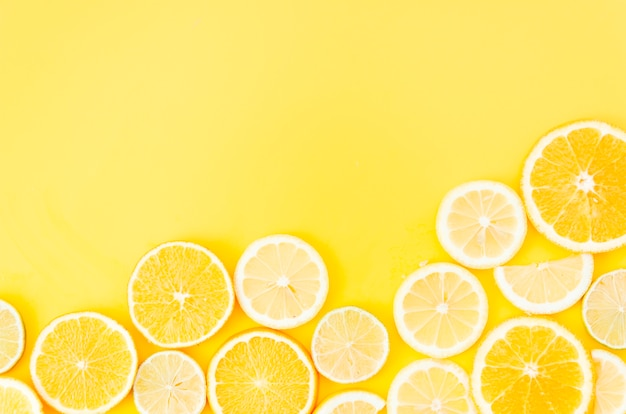 Círculos de frutas cítricas em fundo amarelo