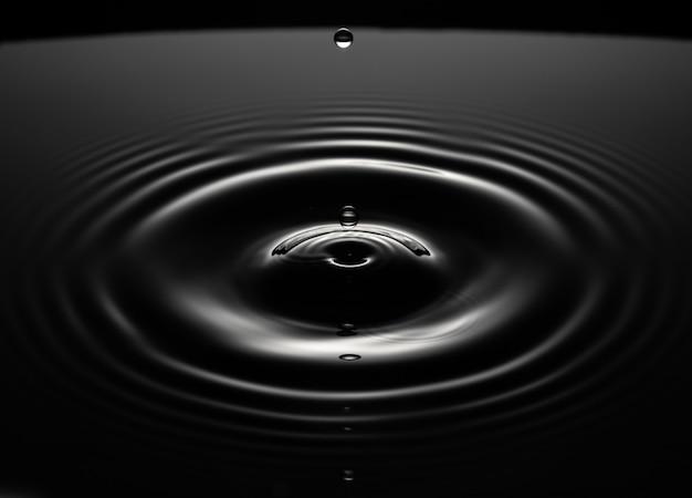 Círculos na água divergem em um círculo, uma gota de água