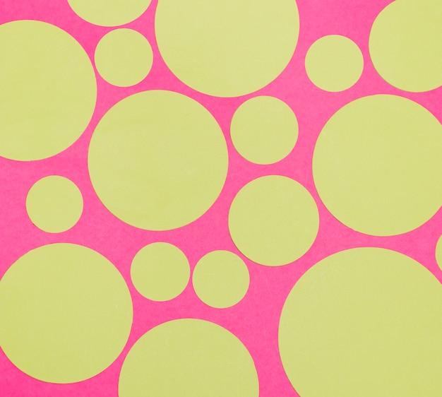 Círculos pequenos e grandes em branco sobre fundo rosa