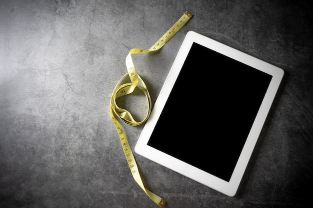 Circunferência da cintura com tablet no chão