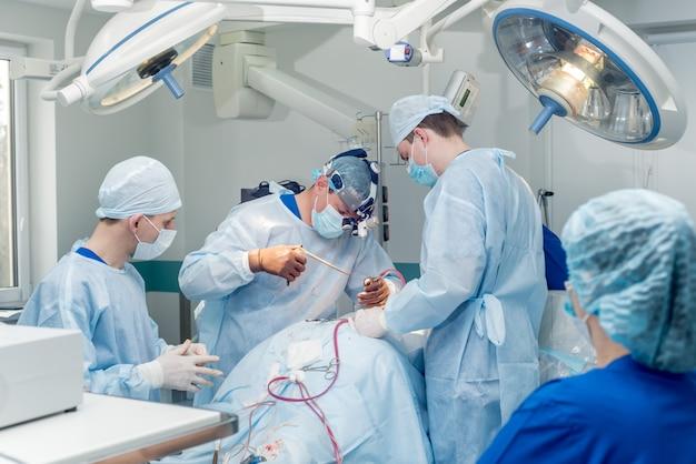 Cirurgia da coluna vertebral. grupo de cirurgiões na sala de cirurgia com equipamento cirúrgico.