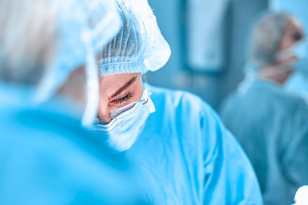 Cirurgia, medicina e conceito dos povos - grupo de cirurgiões na operação na sala de operações no hospital