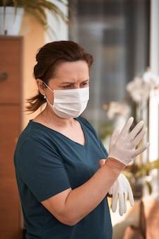 Cirurgiã ou enfermeira vestindo um terno estéril, calçando luvas de borracha estéreis para realizar uma cirurgia,