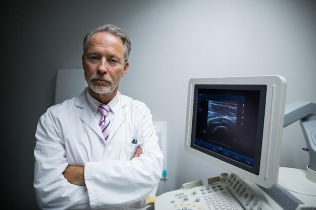 Cirurgião com os braços cruzados em pé perto da máquina do dispositivo ultrassônico
