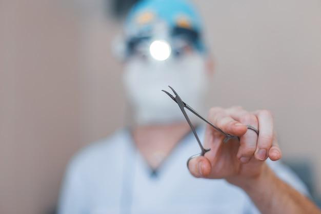 Cirurgião com roupas médicas especiais tem uma tesoura cirúrgica de metal na mão. concentre-se no instrumento. close-up do processo de operação.