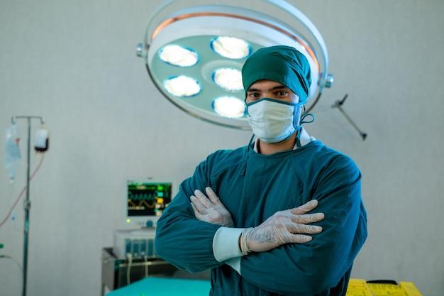 Cirurgião de homem de uniforme pronto para trabalhar na sala de cirurgia no hospital.