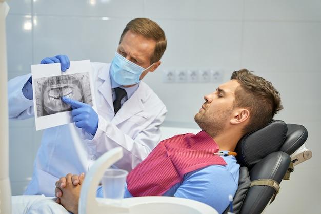 Cirurgião-dentista preocupado segurando uma imagem de raio x perto de seu paciente