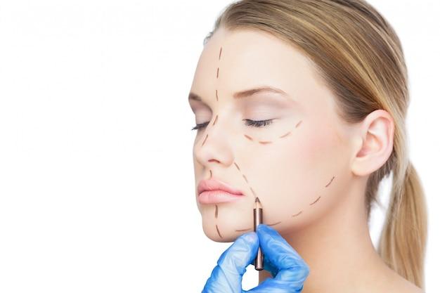 Cirurgião desenhando linhas pontilhadas em paciente fofo