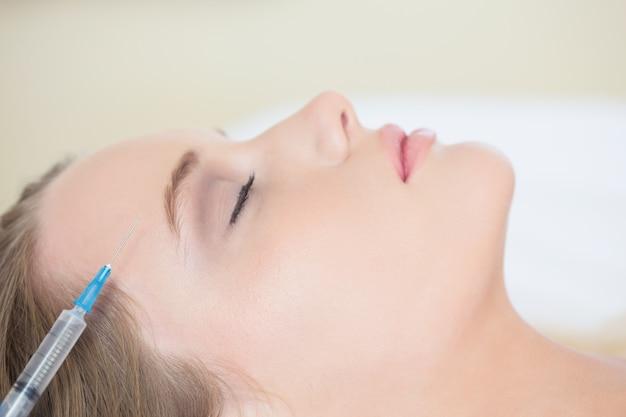 Cirurgião fazendo injeção na mulher relaxada deitada