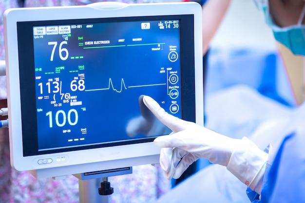 Cirurgião fêmea que usa o monitor na sala de operações.