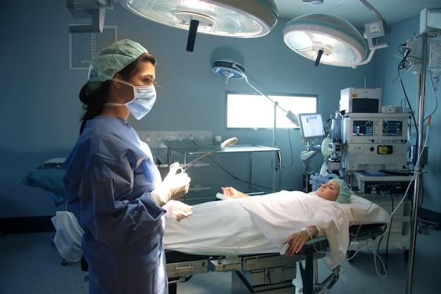 Cirurgião feminino e paciente em uma sala de cirurgia