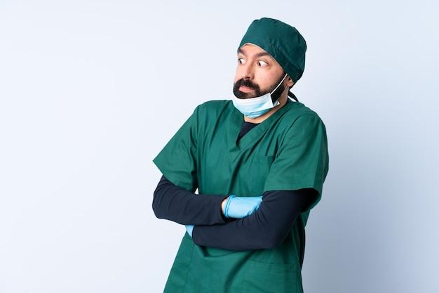 Cirurgião homem de uniforme verde ao longo da parede, fazendo dúvidas gesto enquanto levanta os ombros