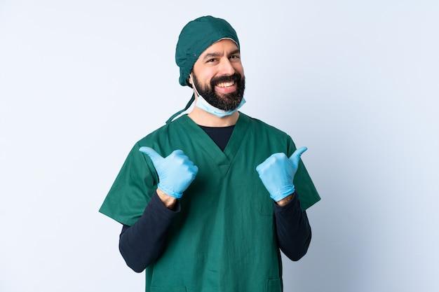Cirurgião homem de uniforme verde sobre parede com polegares para cima gesto e sorrindo
