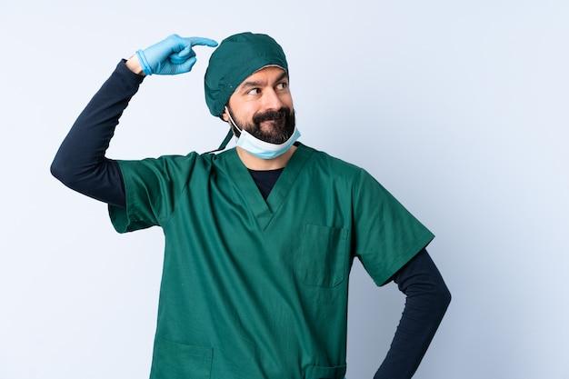 Cirurgião homem de uniforme verde sobre parede tendo dúvidas enquanto coçar a cabeça