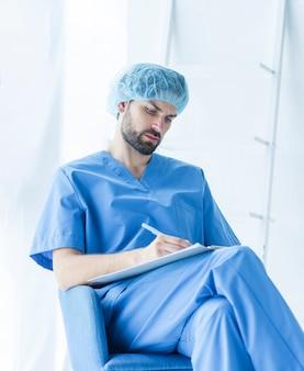 Cirurgião jovem fazendo anotações