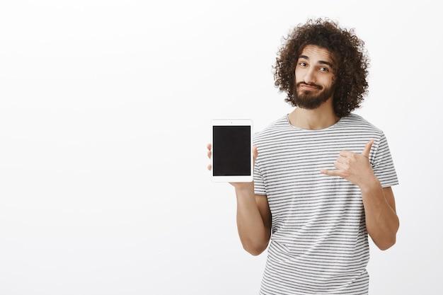 Cirurgião masculino bonito e positivo em camiseta listrada, mostrando tablet digital branco e fazendo gesto urbano