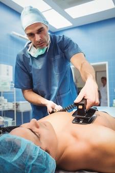 Cirurgião masculino que ressuscita um paciente inconsciente com um desfibrilador