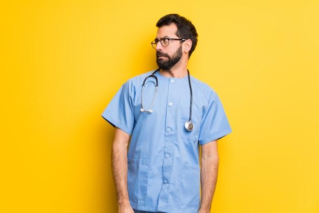 Cirurgião médico homem é um pouco nervoso e assustado pressionando os dentes