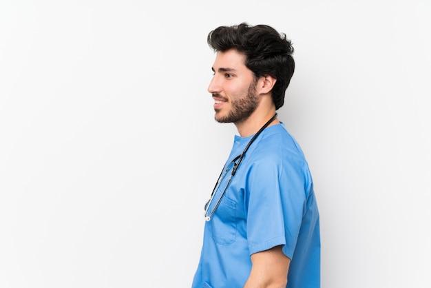 Cirurgião médico homem sobre parede branca isolada em pé e olhando para o lado