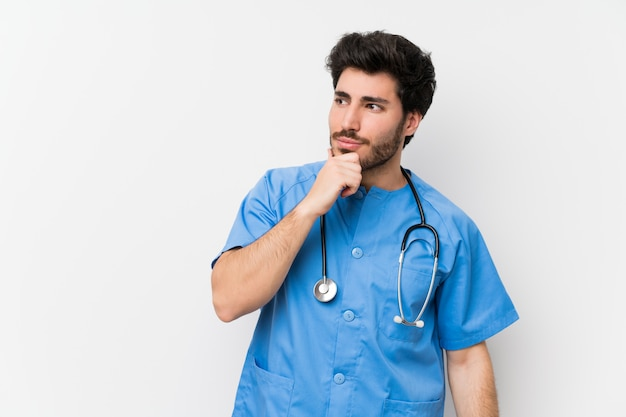 Cirurgião médico homem sobre parede branca isolada pensando uma idéia