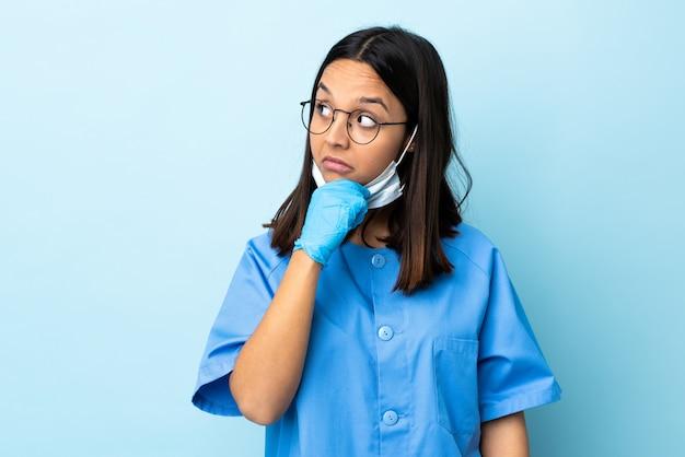 Cirurgião mulher isolada parede azul com dúvidas e com expressão de rosto confuso