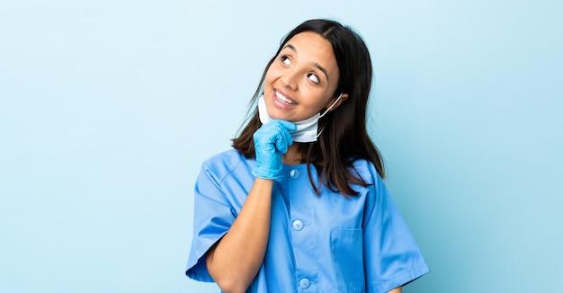 Cirurgião mulher isolada parede azul olhando para cima enquanto sorrindo
