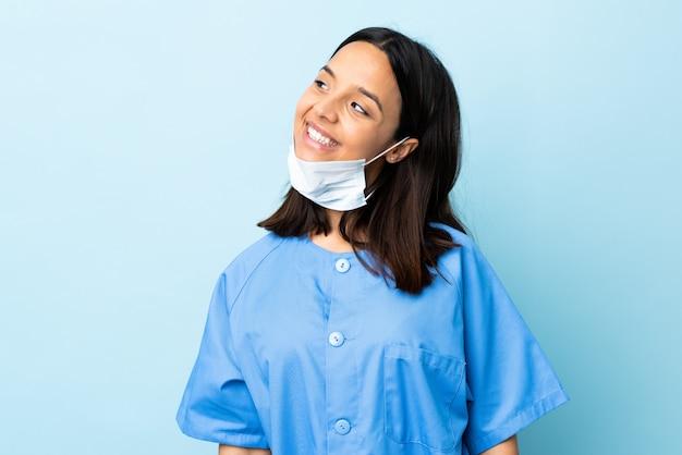 Cirurgião mulher isolada parede azul pensando uma idéia enquanto olha para cima