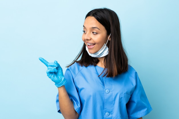 Cirurgião, mulher, isolado, azul, parede, pretendendo, perceber, a, solução, enquanto, levantando um dedo