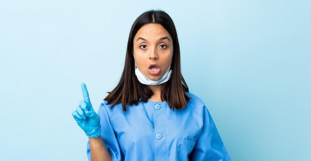 Cirurgião mulher parede azul, que pretende realizar a solução enquanto levanta um dedo