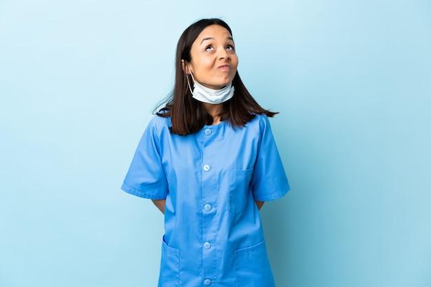 Cirurgião mulher sobre parede azul e olhando para cima