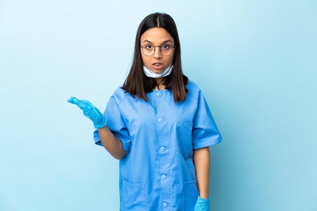 Cirurgião mulher sobre parede azul, fazendo o gesto de dúvidas