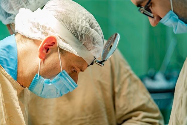 Cirurgião na máscara centra-se na operação no hospital no cercado por colegas.