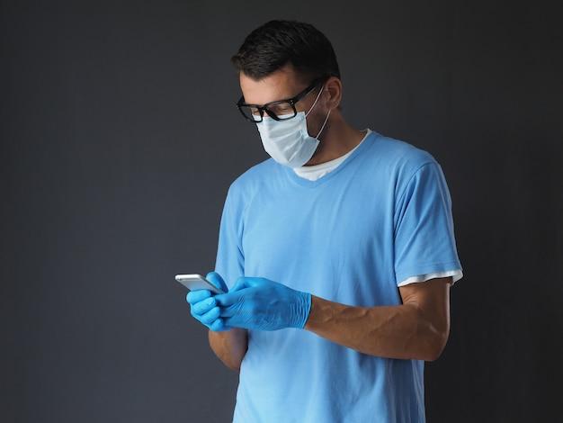 Cirurgião na máscara médica e luvas que texting no telefone celular.