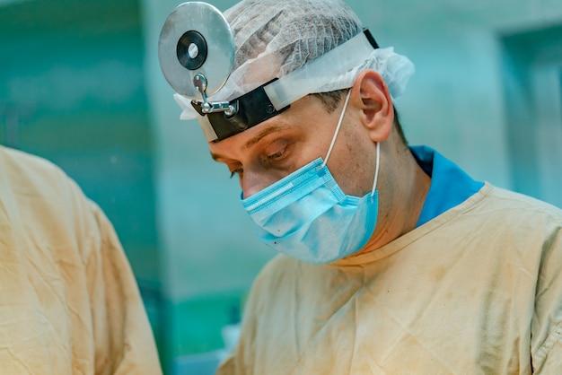 Cirurgião na máscara opera na sala de cirurgia no hospital.