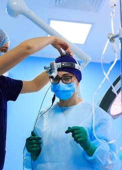 Cirurgião na máscara usando lupas