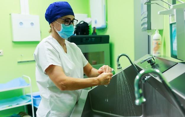 Cirurgião no hospital lavando as mãos