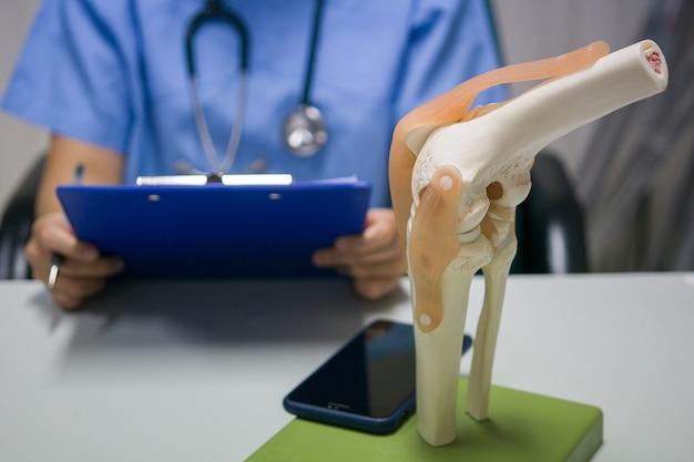 Cirurgião ortopédico lê relatório de substituição do joelho de um paciente