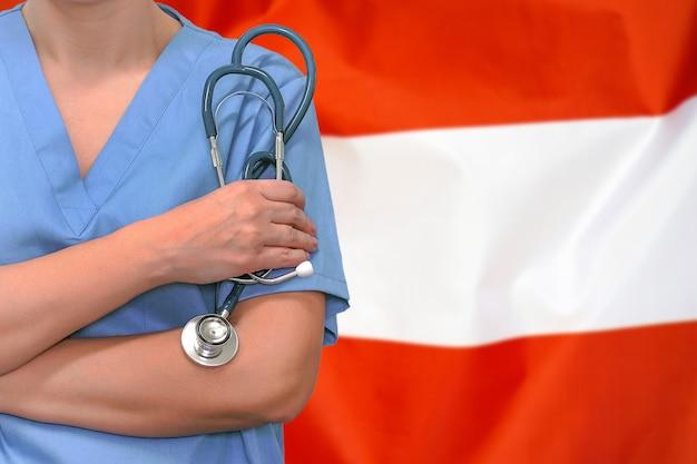 Cirurgião ou médico de mulher com estetoscópio sobre a bandeira da áustria. cuidados de saúde, cirurgia e conceito médico na áustria