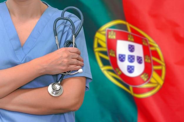 Cirurgião ou médico de mulher com estetoscópio sobre a bandeira de portugal. cuidados de saúde, cirurgia e conceito médico em portugal